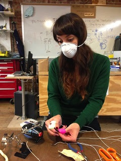 claire soldering wires and wearing a mask